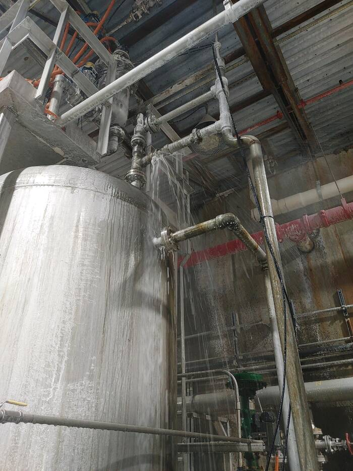 A white tank, covered in grey-brown dust and streaked by liquid pouring out of a pipe above the tank.