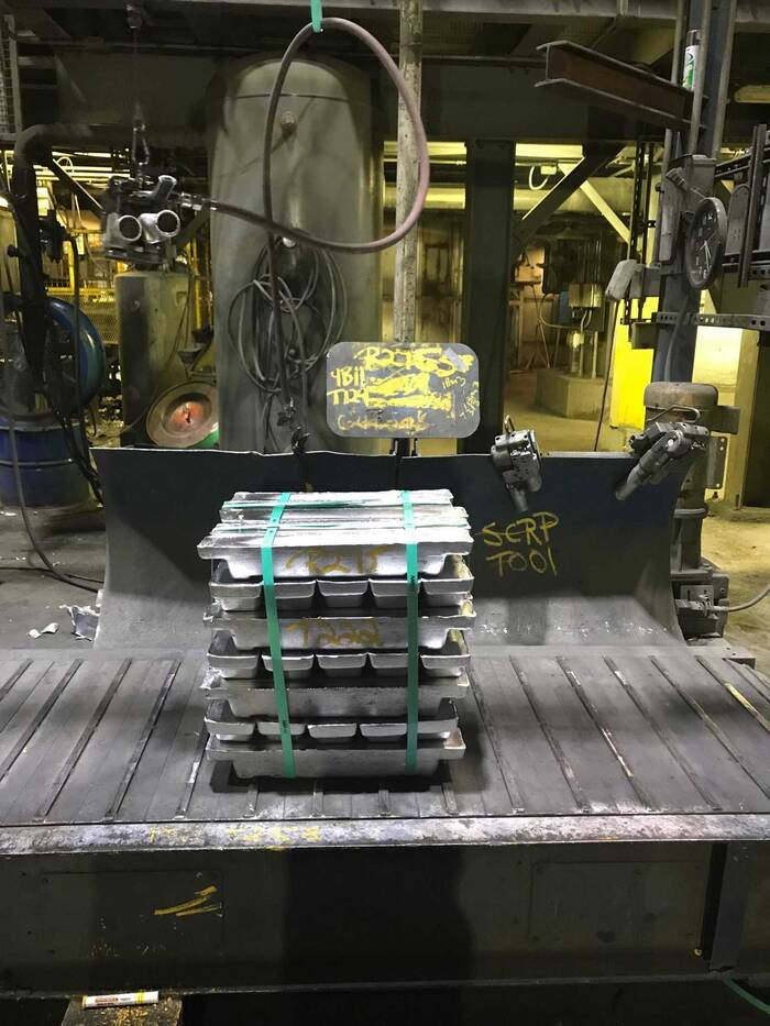 A stack of silver lead ingots sits on a conveyor in the refinery area.