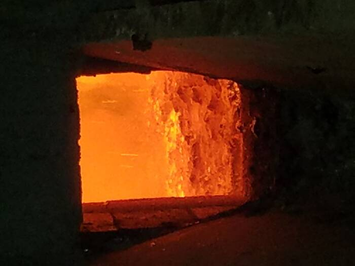 A view into an orange-glowing furnace. Molten lead can be seen inside.