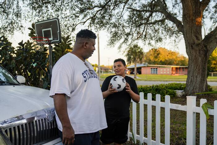 A boy holding a ball with his father standing outdoors, near a basketball hoop.