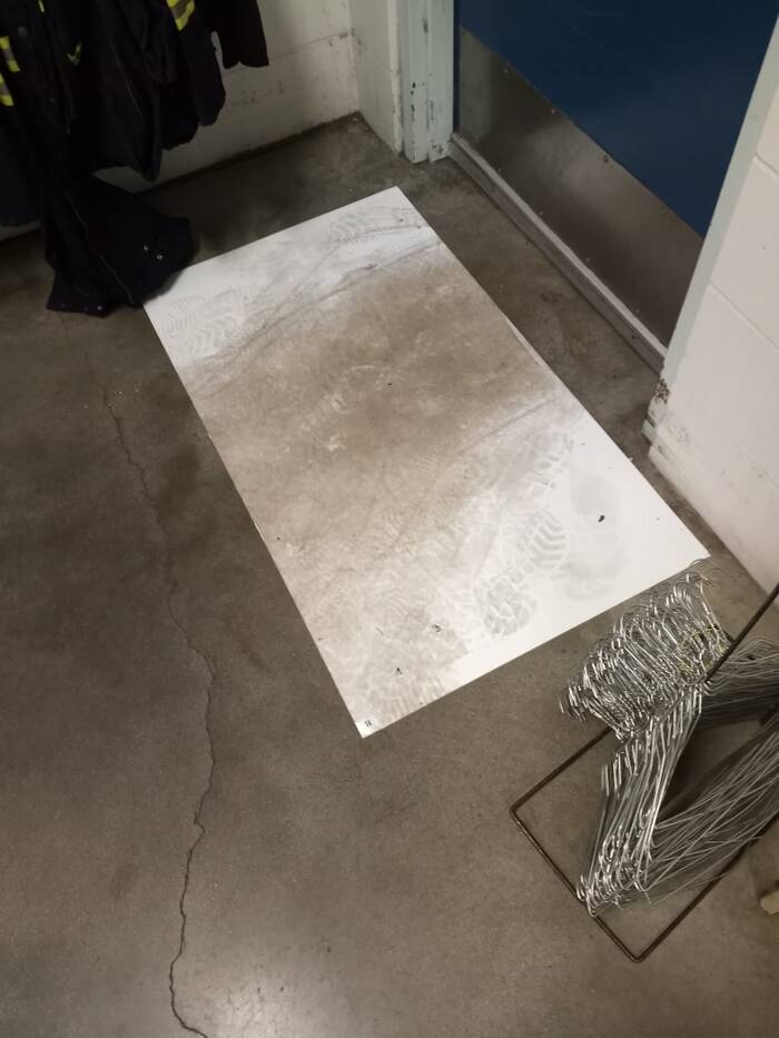 A white mat stained brown and covered in footprints sits on the floor of the employee locker room.