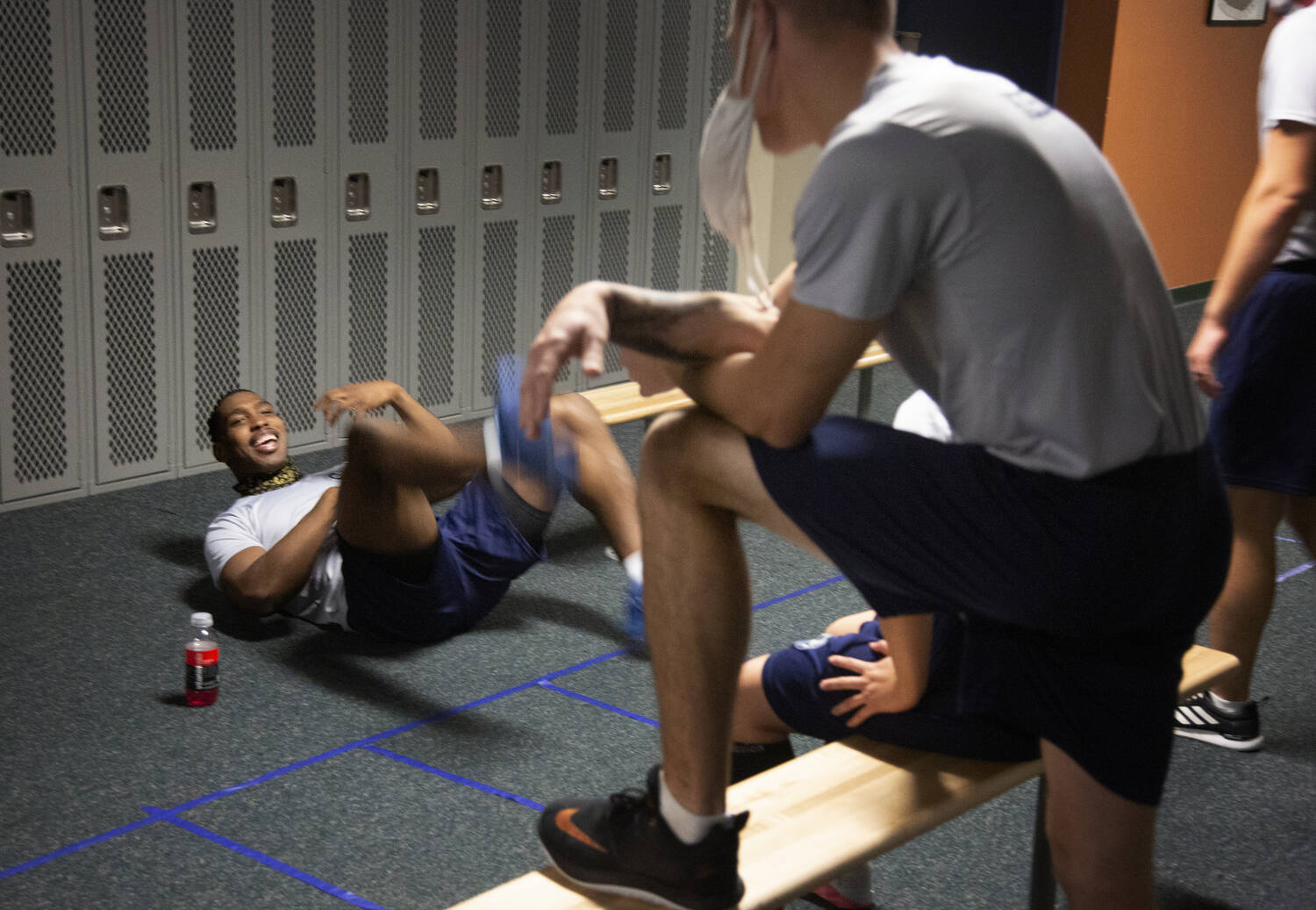 One of the recruits lies on his back in a locker room, laughing with other seated and standing recruits.