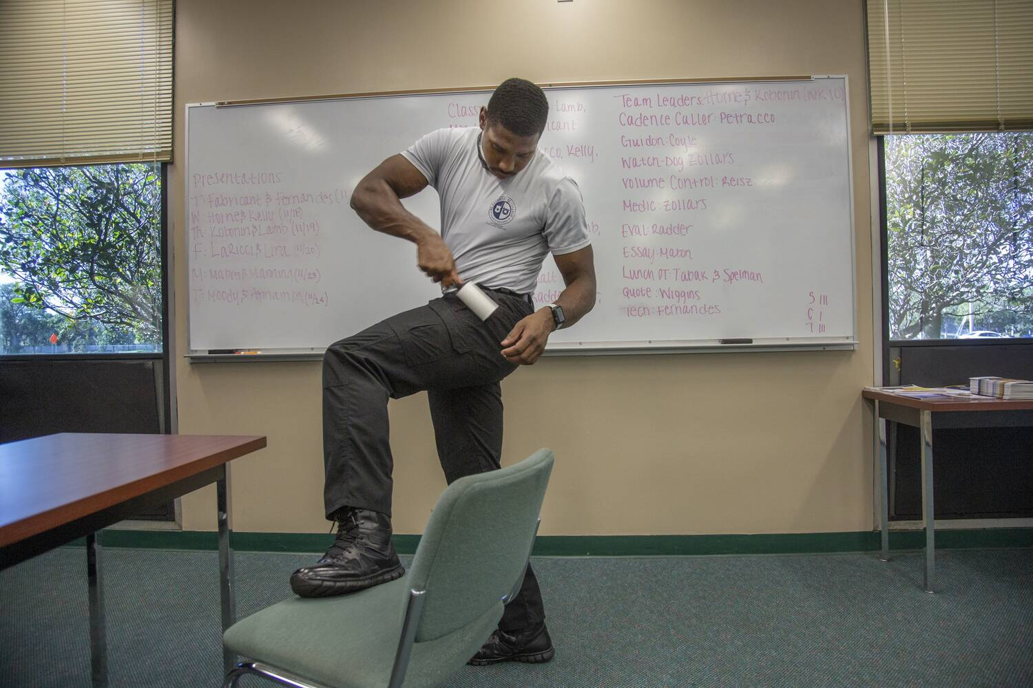 One of the recruits uses a lint roller on his slacks.