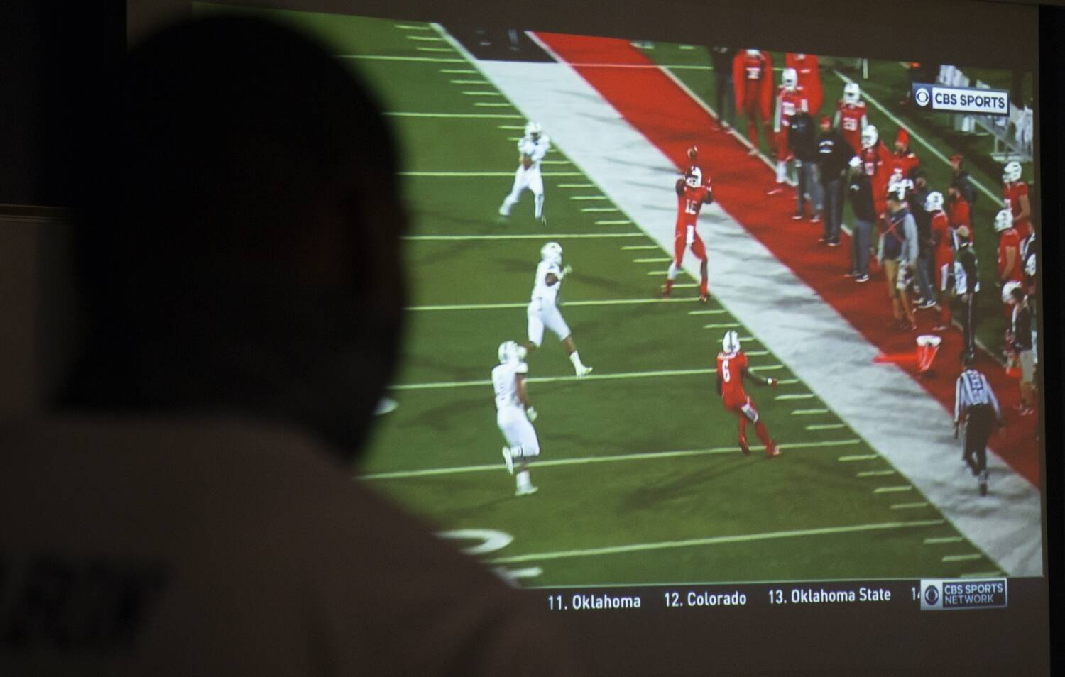 A football game on the TV screen fills the frame, silhouetting a man's head.