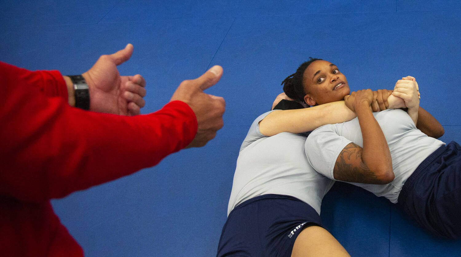 One of the woman recruits, held on the ground in choke hold by another, looks at the instructor, standing above, showing with his hands how she should respond.