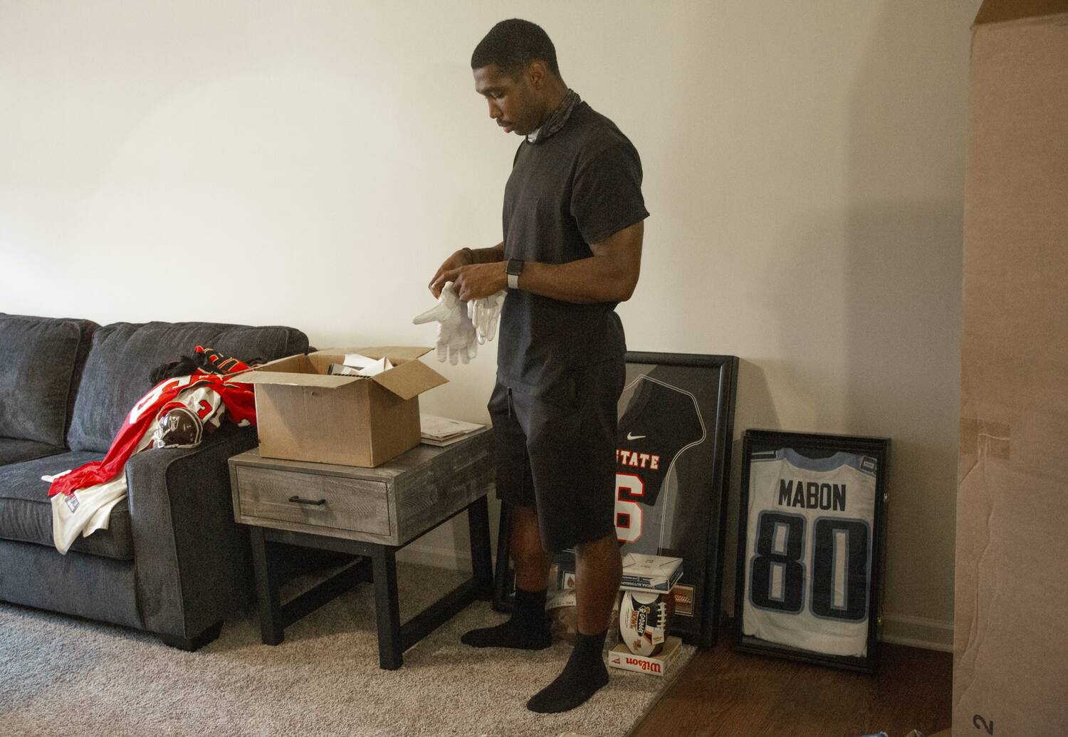 A man stands in a living room, unpacking items from a cardboard box.