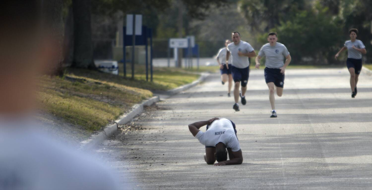 A long view of a street with several runners, the one in front is no longer running, but has gone to his knees, head down with exhaustion.