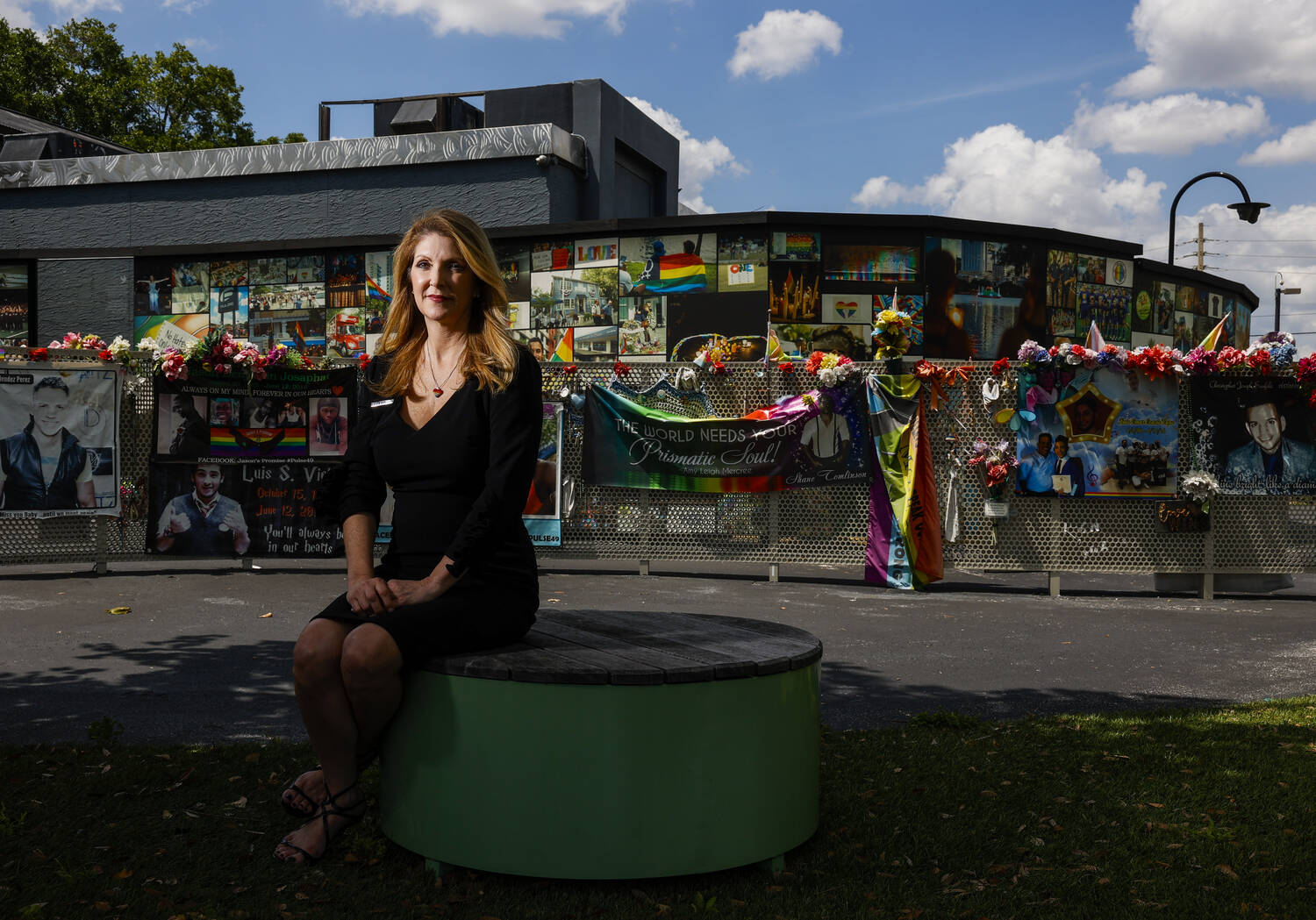 A woman dressed in black sits looking into the camera, Pulse memorials behind her.