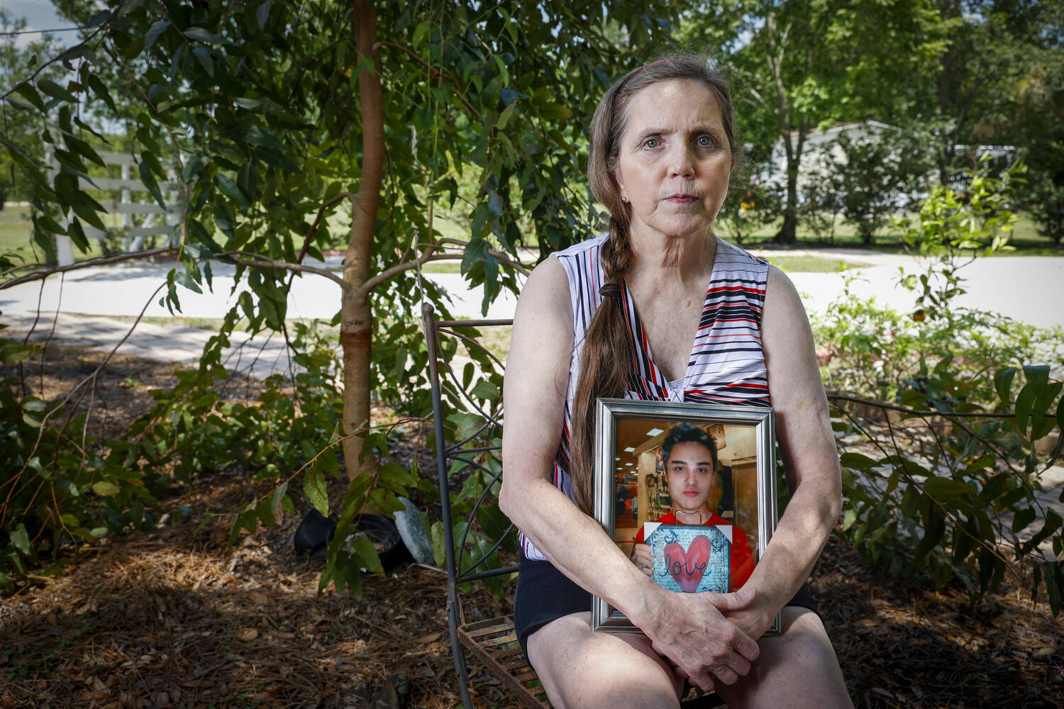 A pensive woman sits on a chair in a garden, holding a portrait of a young man.