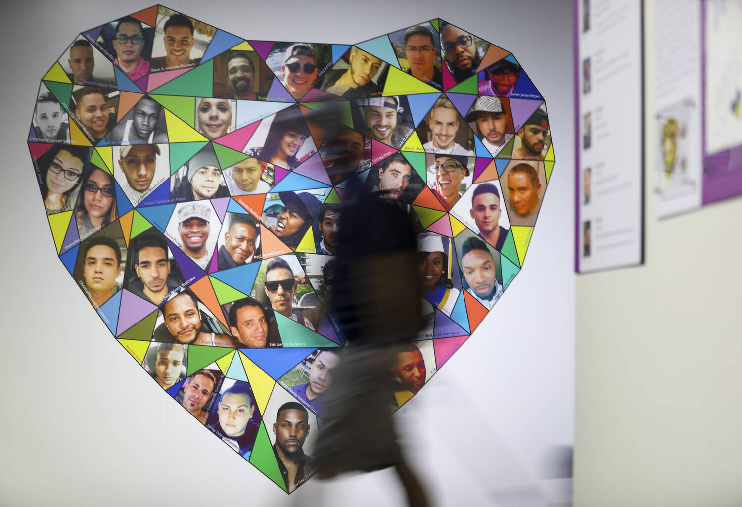 A shadowed figure walks past a heart with the pictures of Pulse shooting victims.