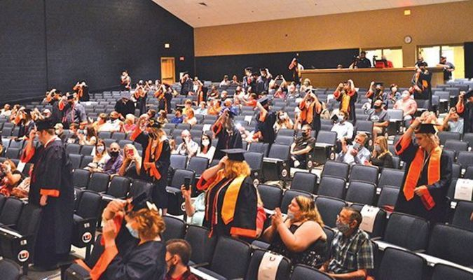 The threat of foul weather pushed Union High School's commencement exercises indoors July 31, where students shown here moved their tassels to signify graduation. KELLEY PEARSON PHOTO