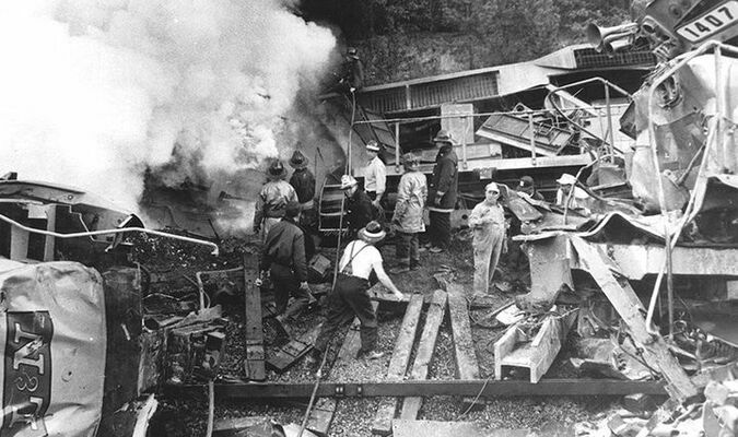 u Workers are tying to contain the fire in unit 1428, out of sight on the left. The crushed remains of SD35 1215 can be seen on the embankment behind. Lead unit on the northbound freight, C628 number 1407, is on the right. (Photo courtesy the Knoxville News-Sentinel)