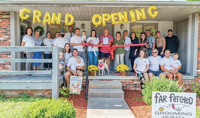 Far Fetched Grooming officially opened Sept. 9. Big Stone Gap Town Council passed a proclamation Sept. 14 welcoming the business, owned by Kaylyn Laws.  Pictured are Laws (center, white shirt) and Mayor Gary Johnson (center, red shirt) with family, friends and council members.   KED MEADE PHOTO