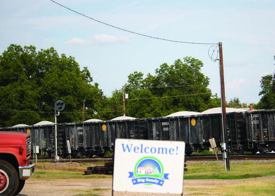 Railfans can catch a glimpse of a sign welcoming viewers to Big Sandy, TX.  Photo by Theresa Olson.