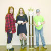 Debbie Dyess (left) presented a traveling trophy to Bluebonnet 4-H Club members Colleen Dover and Elijah Russell for winning first place during the Spooktacular Bull Bash greased pig chase, held in October. Bluebonnet 4-H also received $250 for having the winning duo.