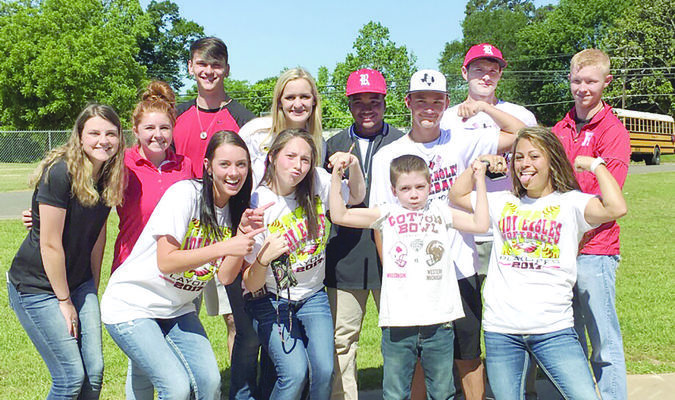 Members of the Rusk baseball and softball teams show off their strength standing next to Caleb Whitely (front row, third from left). Caleb, a third-grader, has beaten two forms of leukemia. The teams recognized him by naming him an honorary captain for their playoff games – baseball against Spring Hill and softball against Atlanta. Caleb threw out the first pitch at game one of the Rusk-Spring Hill game.