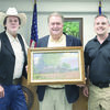 Artist Raymond Ryan (left) and Angelina County Constable Trey Trevathan (right) presented Judge Chris Davis with a print of the Maydelle General Store that Mr. Ryan painted while working in the area.