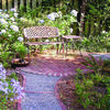 A gray pea gravel path edged with bricks leads to a quiet garden spot. Blue hydrangeas and Lily of the Nile brighten the area.