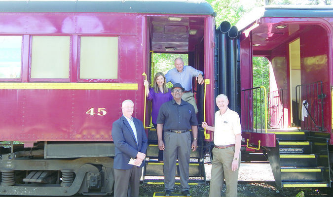 Bob Goldsberry poses with Rusk City Council members Walter Session, Don Jones and Ben Middlesbrooks along with Rusk Mayor Angela Raiborn on one of the passenger cars after receiving the check paying off the loan.