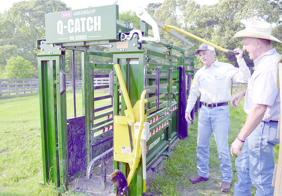 Mr. Selden (left) demonstrates his new cattle chute to Preston Lindsey, director of zone 1 of the Cherokee County Soil & Water Conservation District.