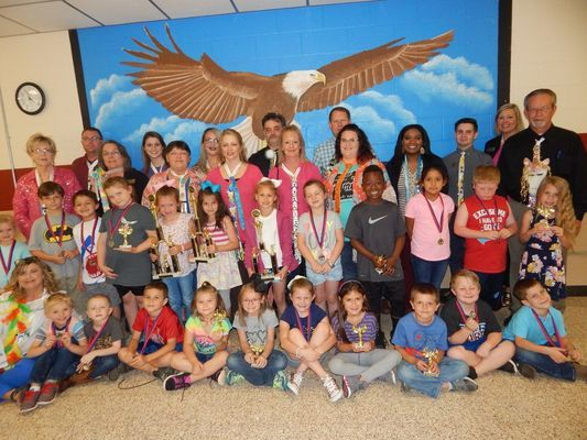 Students pose with  members of the community modeling their ties after receiving awards for the Tacky Tie Contest