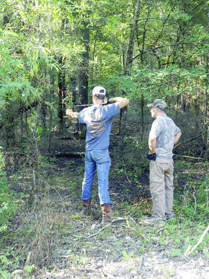Courtesy Photo William Hunt prepares to take a shot during the third annual bow shoot held by the Wells FFA Booster Club as David Seymore, owner of Seymore Outdoors in Wells an event sponsor watches on.