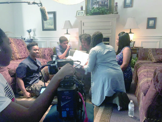 Courtesy photo Alto resident Shanelle Gaddis, pictured far right, with cast mates and crew of the short film 'Black Bones,' discuss the nuances of the movie's script during the two-day filming of the movie in July at Wiley College in Marshall.