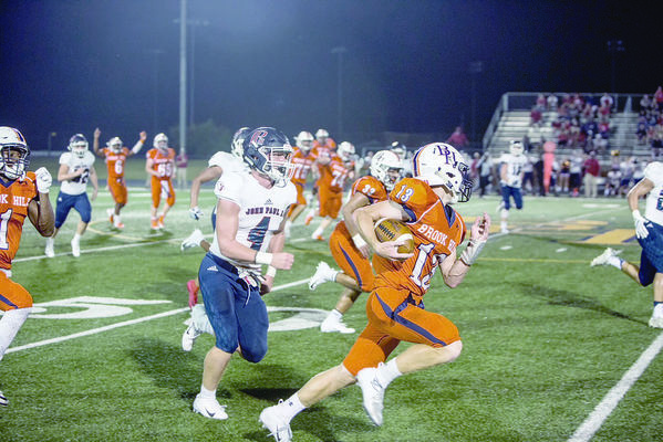 Courtesy Photo Brook Hill Guard No. 13 Fisher Bass runs past No. 4 from John Paul II during Friday night's game.