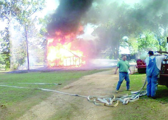 Courtesy Photo Gallatin Volunteer Fire Department members prepare to attack a house fire in Cherokee County in 2011.