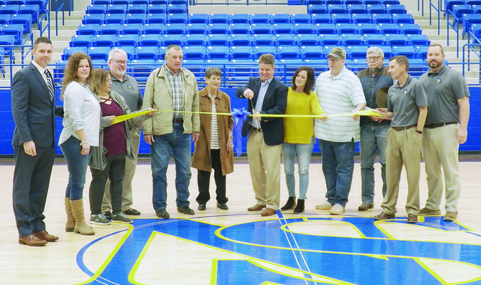 Photo by Michelle Dillon Superintendent Brian Nichols, board members Glenna Weaver and Missy Tennison; Dr. Craig Wilcox, Curriculum and Special Programs Director; board members Joe Taylor, Lolita Davis, Lori Lawon, J.B. Neely and Michael Davis; Joe Brandon, junior high principal; and Josh Faucett,  high school principal all gather around former superintendent Dr. Gregg Weiss as he cuts the ribbon for the official opening of the New Summerfield Coliseum.
