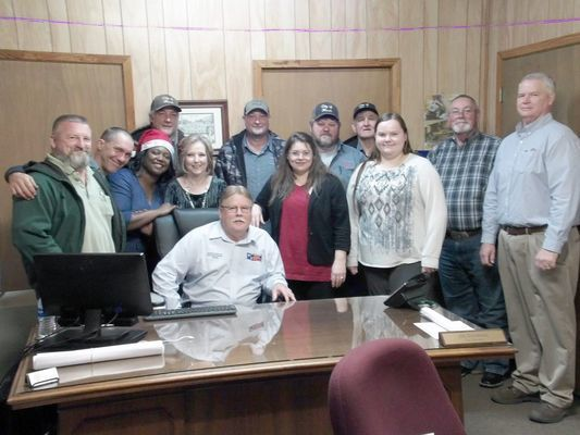 Photo by Cristin Parker Rusk city employees gather to bid adieu to Rusk Building Inspector and Code Enforcement Officer Cliff McElfresh, seated, last week. Pictured, from left, are Rusk Utilities Director Thomas Thompson, Utilities Department crewman Michael Beck, City Secretary Rosalyn Brown, Utilities crewman Ched Willis, Utilities Billing Manager Pam Tyer, Utilities crewman Ray Dosser, Utilities billing clerk Beverly Brister, Roger Stewart, Public Works crewman Howard King, Account Manager Brittany Stith, City Manager Jim Dunaway and Rusk Economic Development Director Bob Goldsberry.