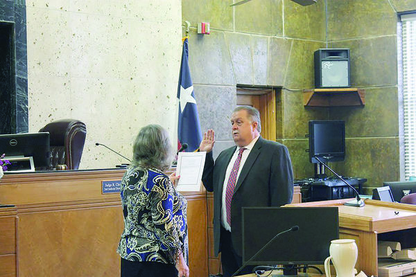 Courtesy photos County Judge secretary Peggy Cornelius swears Cherokee County Judge Chris Davis into office on Tuesday, Jan. 1, in the county courtroom at the Cherokee County Courthouse in Rusk.