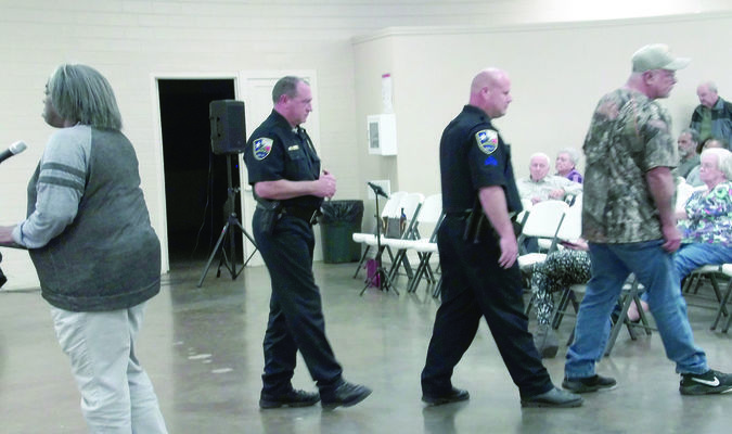 Photo by Cristin Parker Rusk Police Chief Joe Williams and Sgt. Nathan Acker escort George Stover from the Rusk meeting on Dec. 27.