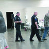 Photo by Cristin Parker Rusk Police Chief Joe Williams and Sgt. Nathan Acker escort George Stover back to his seat during the Rusk meeting on Dec. 27.