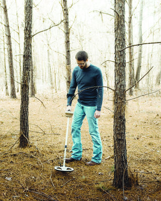 Filmmaker Brackston McKnight uses a metal detector on his property, searching for lost treasure.