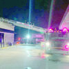 Courtesy photo Jacksonville firefighters use the department's ladder truck to bridge the span to the roof of a Jacksonville convenience store which caught fire recently.