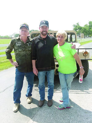 Courtesy Photo Tom Townsend, left, and his wife Jan, right, recently worked with Chuck Norris and the History Channel by providing their Humvee for the channel's show 'Epic Guide to Military Vehicles'.
