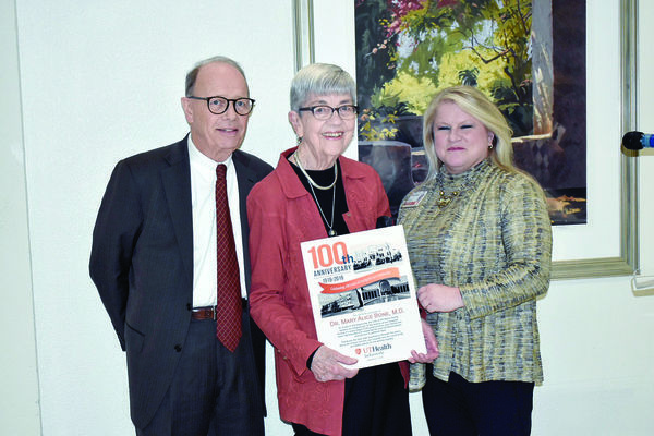 Photo by josie fox Dr. Mary Alice Bone, center, shows off the commemorative keepsake UT Health presented her during the healthcare system's 100th anniversary reception. Also picured are UT Health-Jacksonville CEO DeLeigh Haley, right, and UT Health-Jacksonville Board of Trustees Chair Joe Angle.