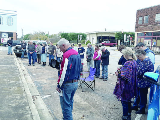 The small but enthusiastic crowd of local patriots and veterans attending the local Veterans Day ceremony on Monday bows their heads to pray.