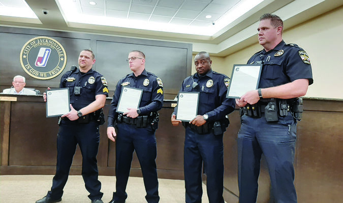 Photo by Michelle Dillon From left, Jacksonville Police Department Sergeants Randy Wilson and Steven Markasky, and Officers Quincy Hamilton and Benton Brumit show off their ommendations during a recent council meeting.