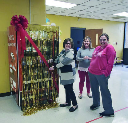 Photos by Josie Fox From left, Rusk Elementary Library assistant Angela Corley, Assistant Principal Ashley Oliver and parent Kandi Wilkerson cut the ribbon to unveil Rusk Elementary's new book vending machine.
