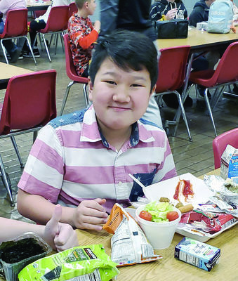 Photo by Josie Fox RISD sixth grader Robby Calliahan is all smiles as he samples possible new  menu items.