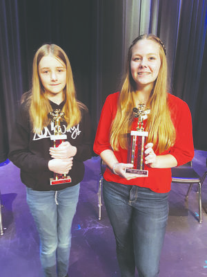 Photo by Cristin Parker Elizabeth Arrington, right and Kaylie Martin show off their trophies after participating in the 2020 County Spelling Bee.
