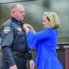 Photo by Josie Fox Amy Williams, right, pins his new badge on her husband, JPD's new Chief Joe Williams, left.
