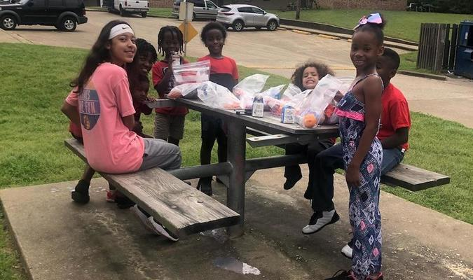 Rusk students enjoy a picnic after scoring their lunches.