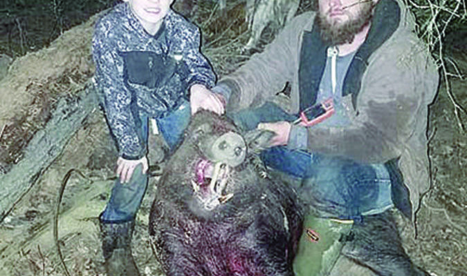 Courtesy photo Jesse and Randal Grimes bag a feral hog in a hunt this time last year. Jesse is now battling liver cancer.