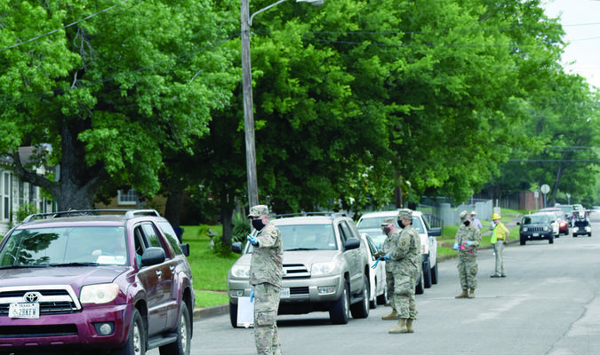 Good Samaritan volunteers, National Guardsmen and city officials help direct traffic lined up along Sycamore Street during the May 13 food distribution. A second event is planned for Wednesday, May 27 at Good Samaritan, 190 W. Second St., Rusk. Any local resident that is food-insecure can receive food boxes.