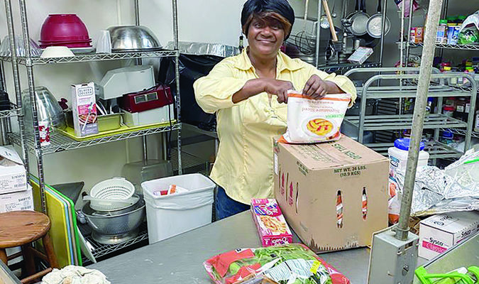 Courtesy photo Sylvia Mae, sole owner and head chef of Jacksonville's Sylvia Mae's Soul Food Restaurant gets ready to start prepping for meal service at HOPE's Community Kitchen recently.