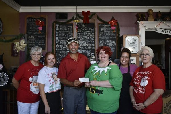 Photo by Josie Fox Rusk Chamber of Commerce Vice President Mark Raiborn, center, accepts a $500 donation from the Daily Grind owner Rachel Loden recently. Also pictured, from far left are Daily Grind employees LaDonna Sparkman, Emily Duke, Billie Seeton and Karen Loden.