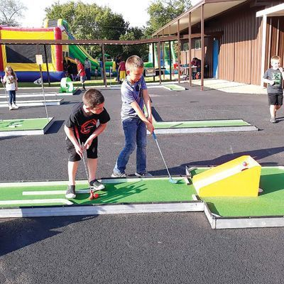 Photo by Jo Anne Embleton  Youths try their hand at putt-putt golf, on a course set up at Alto's Hillside Baptist Church during a recent unity event at the church.